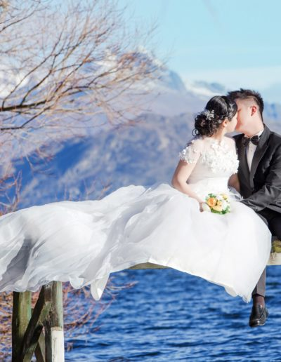 Bride and Groom Sitting on Pier over lake in picturesque setting